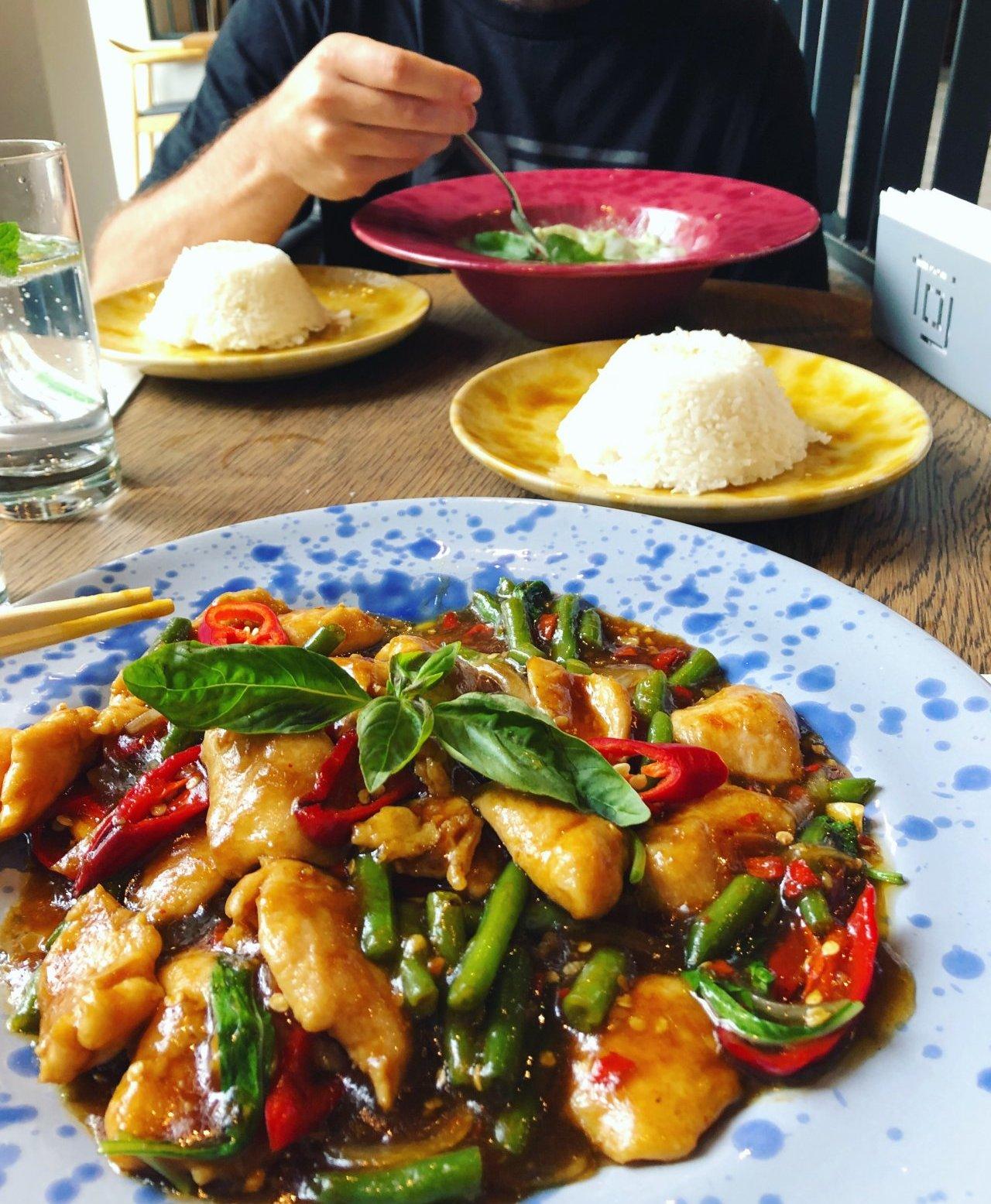 kurczak z woka z tajską bazylią na niebieskim talerzu, na drugim planie zielone curry i dwie porcje ryżu