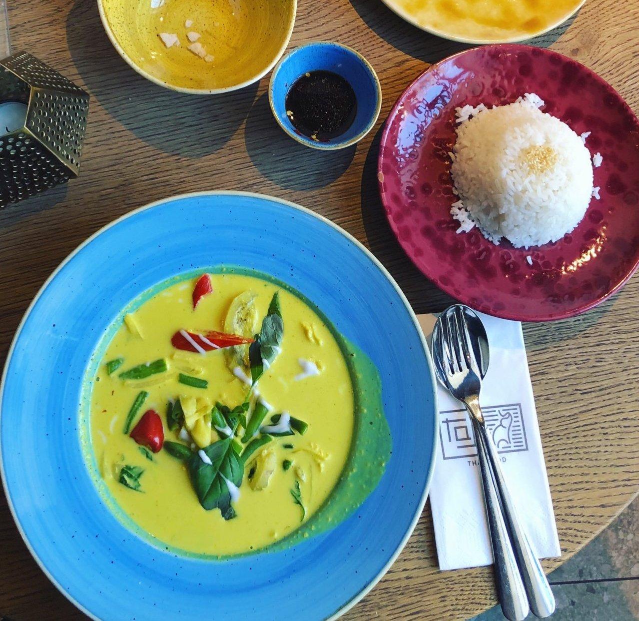 zółte curry na niebieskim talerzu, obok dwie porcje ryżu