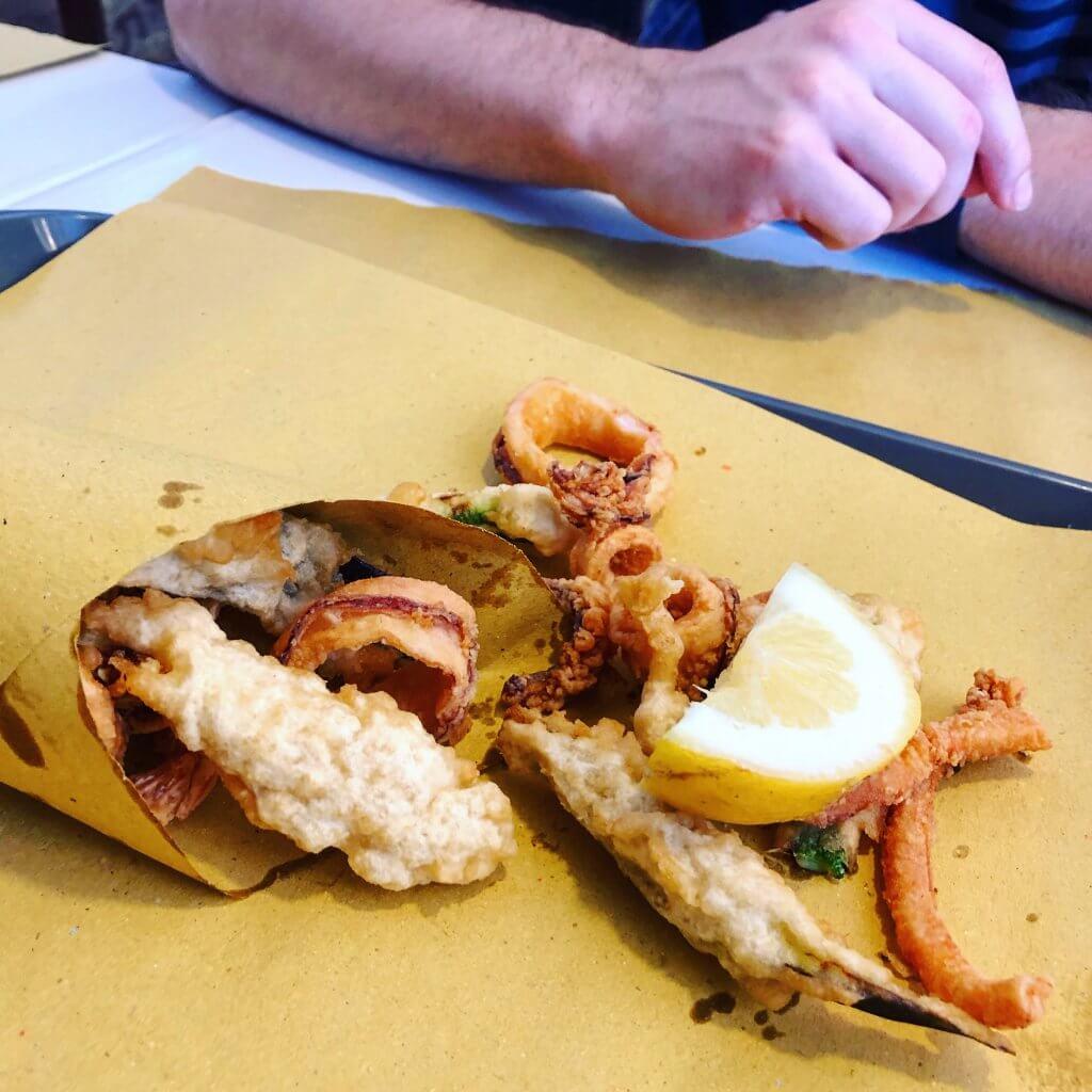 na zdjęciu owoce morza w panierce, podane z cytryną na papierze