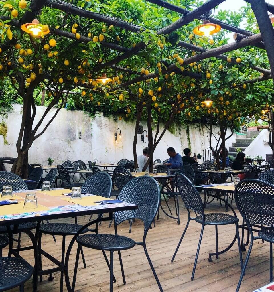 na zdjęciu widok ogródka - metalowe krzesła i stoły na świeżym powietrzu
