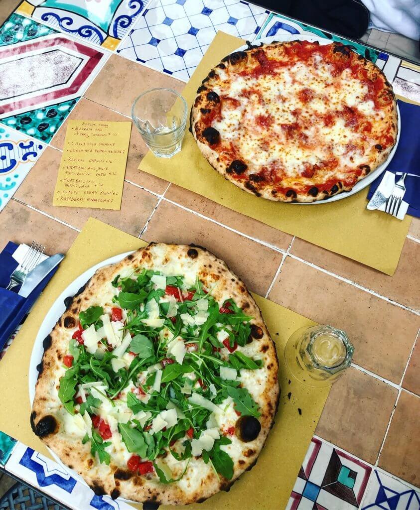 na zdjęciu dwie pizze - margarita z mozzarellą i drugą z rukolą, płatkami parmezanu i pomidorkami koktajlowymi